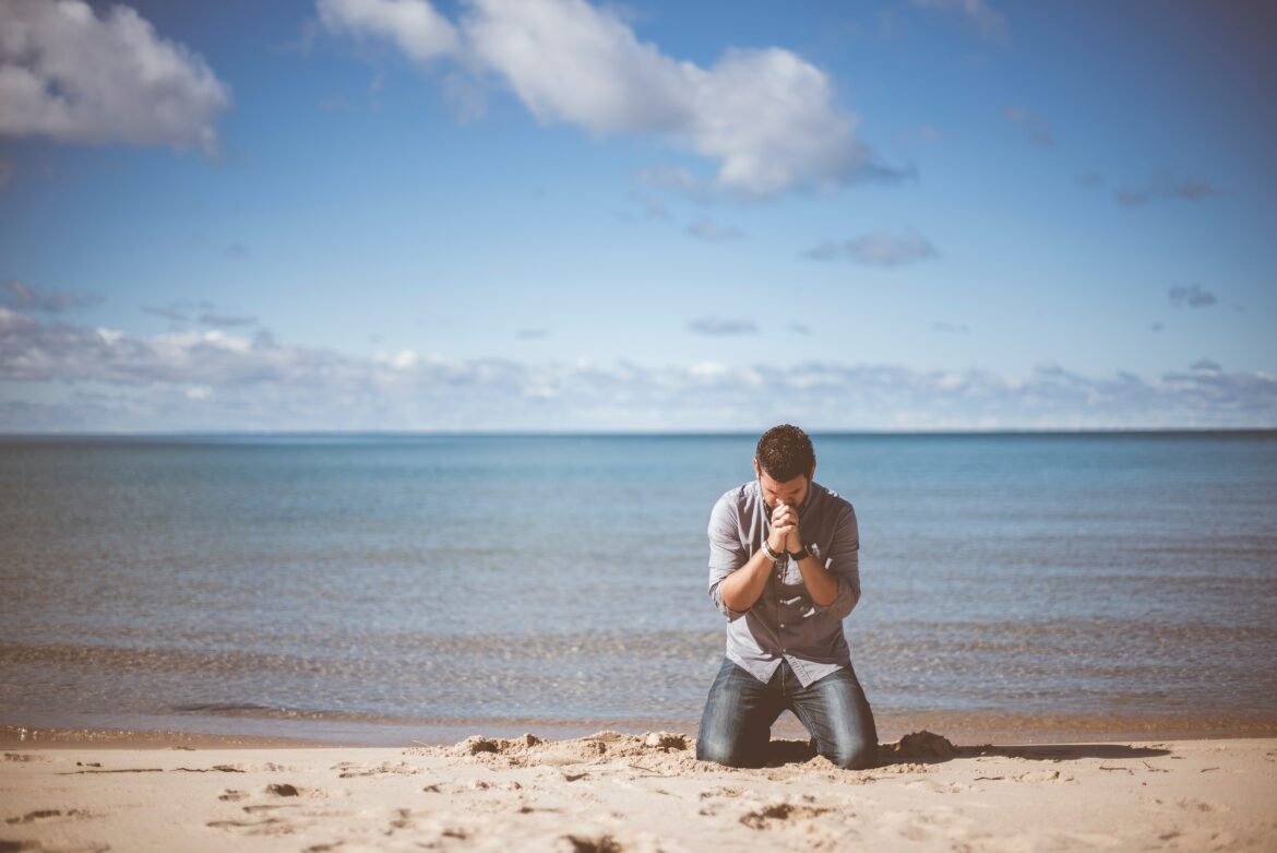 man kneeling on beach thinking about life